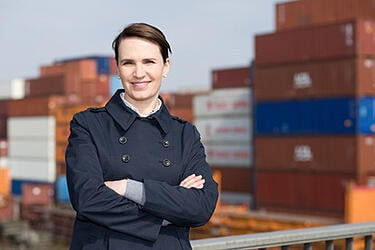 woman_in_front_of_cargo_containers