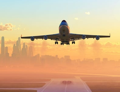 Plane_taking_off_with_skyline_in_back